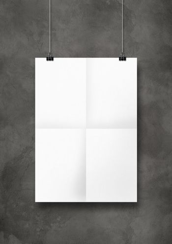 White folded poster hanging on a concrete wall with clips
