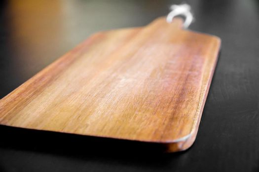 Wooden cutting board on black table