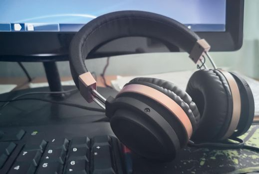 Stereo headphones on the keyboard of a computer