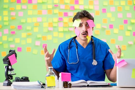 Young doctor with many reminders and urgent work