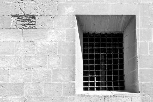 Window with wrought iron grille on the facade of Santa Maria church