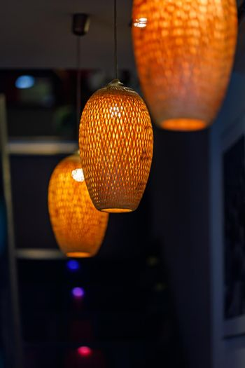 Orange lanterns in the form of a straw chandelier in a dim room.