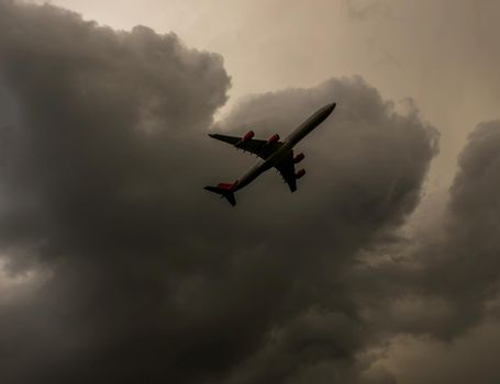 Passenger plane flying in the blue sky with clouds, cruise aircraft, transport industry