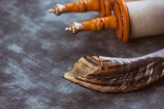 Shofar horn jewish religious holiday symbols on soft focus Jewish torah scroll