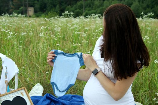 Pregnant woman in white t-shirt holding a blue baby bodysuit