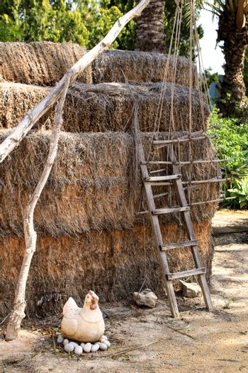 Straw bales stacked next to wooden ladder