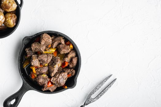 Bangin beef stew, in cast iron frying pan, on white stone surface, top view flat lay, with copy space for text