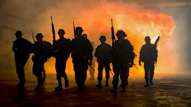 Silhouettes of soldiers during Military Mission at dusk Silhouettes of army soldiers in the fog against a sunset, marines team in action, surrounded fire and smoke, shooting with assault rifle and machine gun, attacking enemy