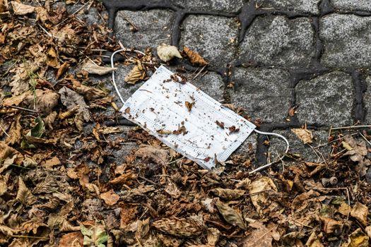 Surgical white masks on the ground. Corona virus pollution. Leherheide, Bremerhaven.