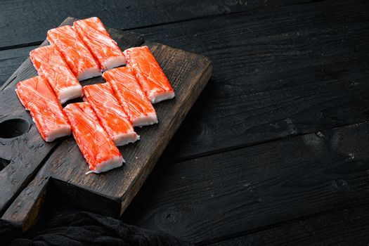 Fresh Crab meat surimi with blue swimming crab, on wooden cutting board, on black wooden table background , with copyspace and space for text