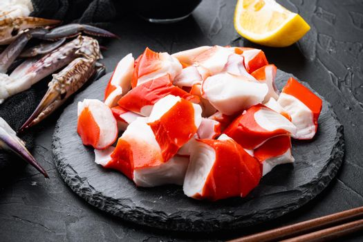 Fresh Crab meat stick surimi , on stone board, on black background
