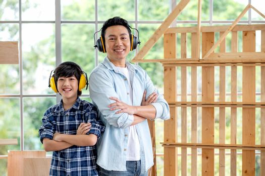Portrait of Asian father and boy with mechanic headphone stand in front of woodwork and look at camera.