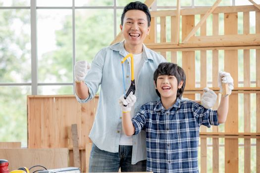 Farther and son express happy and cheerful emotion in room with woodwork and boy hold Hack Saw and piece of wood stand in front of his father. Concept of craftsman family and have good hobby together.