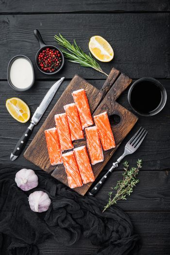 Fresh Crab meat stick surimi with blue swimming crab, on wooden cutting board, on black wooden table background, top view flat lay