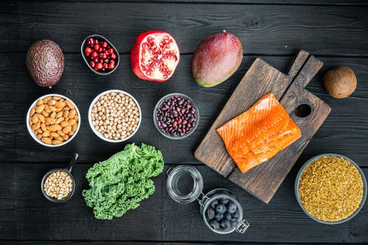 Healthy food clean eating selection, top view, on black wooden background