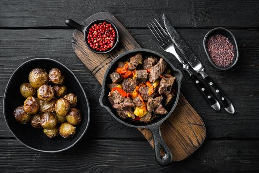 Beef stew goulash - rustic style, in cast iron frying pan, on black wooden background, top view flat lay