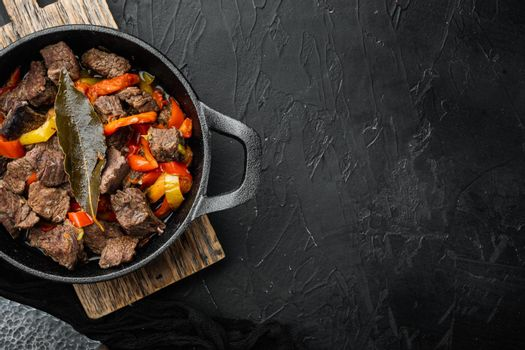 Meat stew with sweet bell pepper and bay leaf, in cast iron frying pan, on black stone background, top view flat lay, with copy space for text