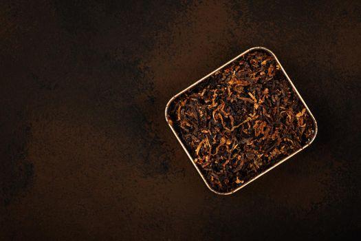 Round tin of coarse cut pipe tobacco over brown