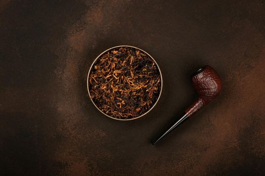 Tin of coarse cut tobacco and pipe over brown