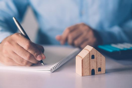Hand of businessman planning and writing on note expense and mortgage with home, insurance house, finance and investment, calculate loan of residential, cost for refinance of property concept.