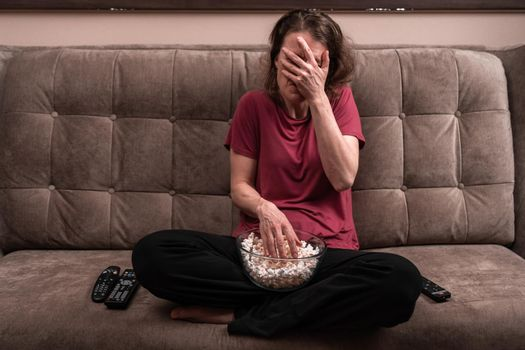emotions when watching TV at home with popcorn. fear and awe