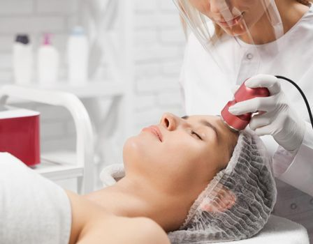 Attractive woman lying on procedure cleaning face.