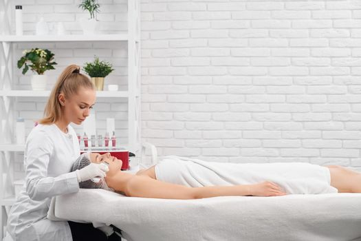 Young woman lying on procedure for cleaning face.