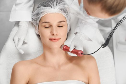 Woman enjoying procedure cleaning or massage for face.