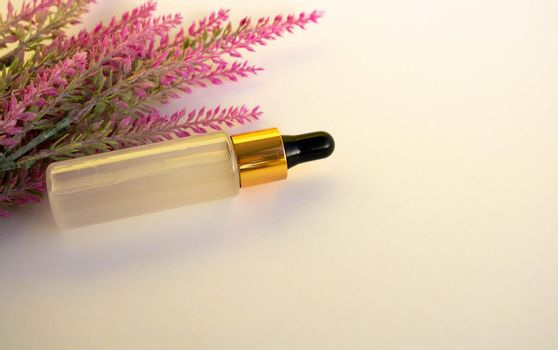 A bottle of cosmetic liquid transparent gel next to a branch of artificial lavender on a white background. Flat styling style