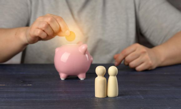 wooden figurines of little men family on the background of a man with a piggy bank. The concept of savings and long-term budgeting