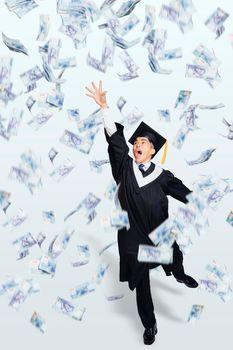 Happy male  graduate student running under money rain