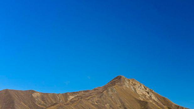 Barren Brown Mountains Against A Blue Sky