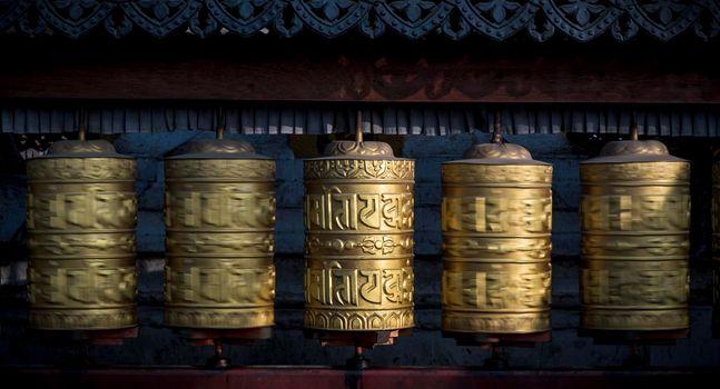 Buddhist shiny prayer wheels rotating in motion