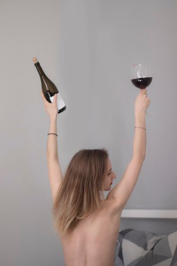 beautiful slender half-naked girl sitting with her back to us, holds a bottle of red wine with no lable and a huge glass a in a bed with gray sheets in triangles
