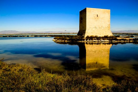 Tamarit tower surrounded by salt lagoons in Santa Pola