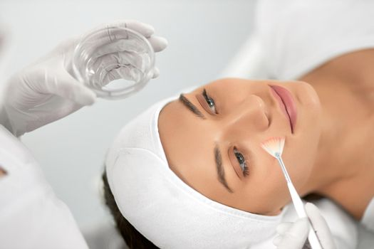 Young woman doing procedure for face in beautician.