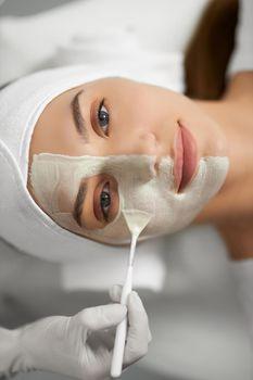 Cute woman lying on procedure for rejuvenation skin.