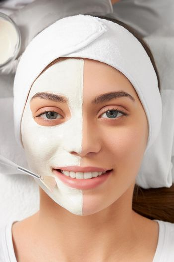 Smiling woman on cleaning face in beautician.