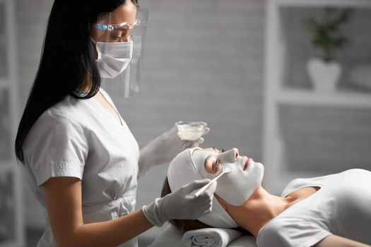 Beautician doing cleaning face with cosmetics for patient.