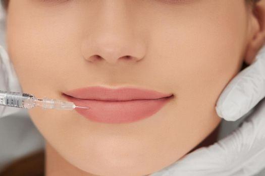 Beautician doing procedure for lip augmentation.