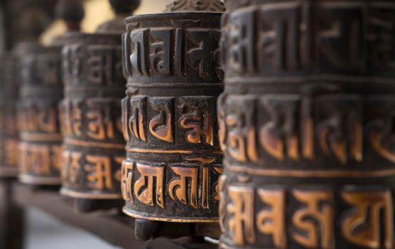 Buddhism obsolete prayer wheels in row