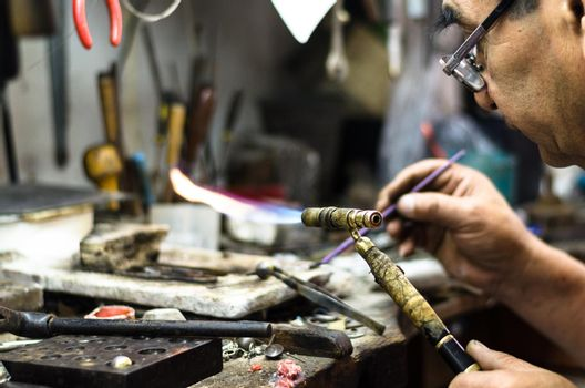 Master soldering jeweller ornament. Picture of hands and product close up.