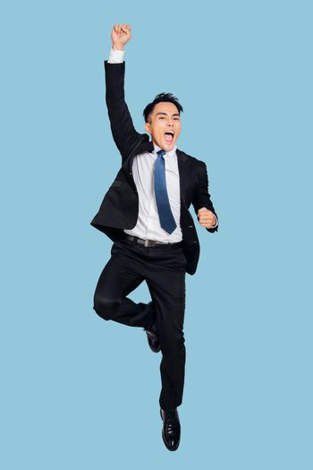 young  businessman jumping in air