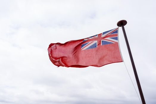 uk red ensign the british maritime flag flown in white sky