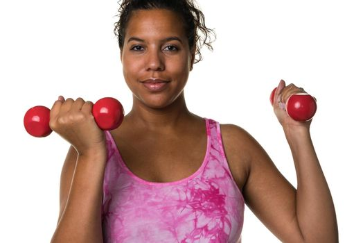 Mixed raced young woman in pink shirt exercising with red 2 kg weights dumbbells isolated in white