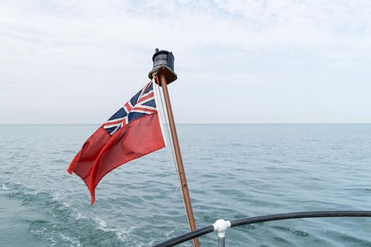 Uk red ensign the british maritime flag flown from yacht with the sea and sky behind it