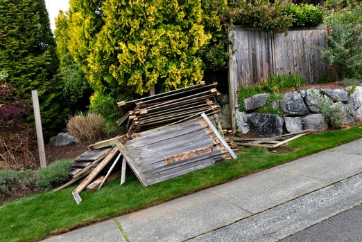 Old wooden fence being tore down to prepare to install new one