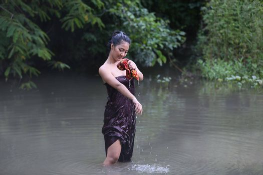 Rural Young Asian Women Bathing In A River, or Portrait Of Beautiful Young Asian Woman Bathing In The River. Asian sexy woman bathing in creek.