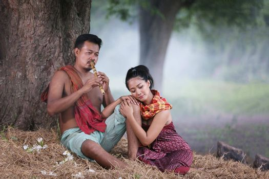 Couple love of Asian Young man and women sitting under tree against buffalo and natural background, rural way of life in the Northeast of Thailand. A young man was blowing a bamboo mouth organ to his lover.