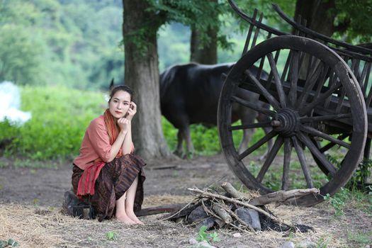 Thai woman farmer wearing local thai tradition sitting on her farm and buffalo  background,countryside Thailand
